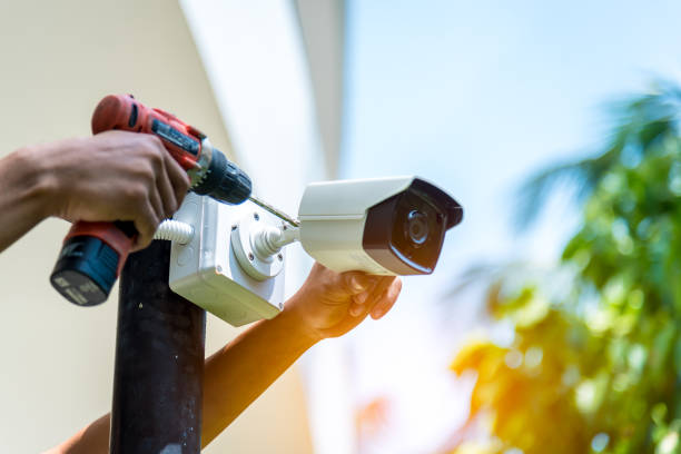 A Wireless CCTV camera setting outside building with white box water poof with sun blur background.